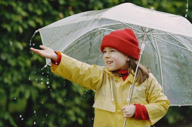 Bambini divertenti in stivali da pioggia che giocano da una pozzanghera