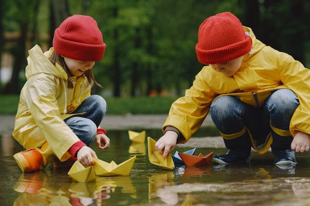 Funny kids in rain boots playing with paper ship by a puddle
