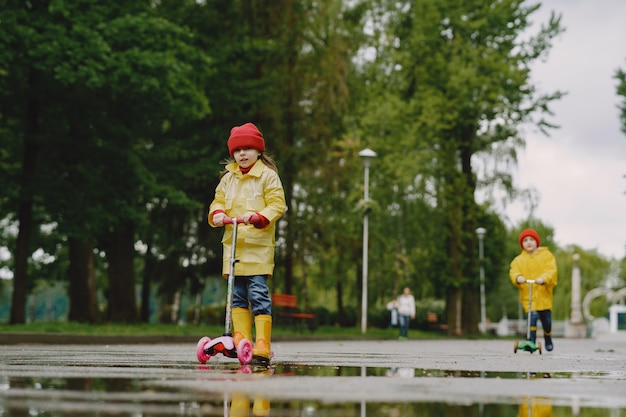 Bambini divertenti in stivali da pioggia che giocano con i pattini