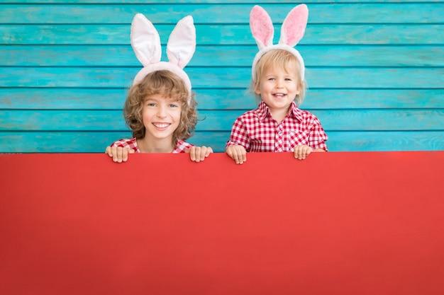 イースターバニーを着ている面白い子供たち。空白のボードを持っている子供たち