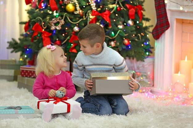 배경에 선물 상자와 크리스마스 트리가 있는 재미있는 아이들