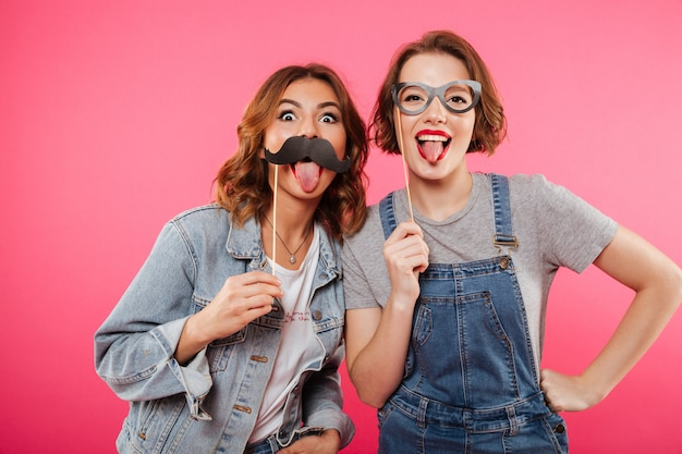 Funny ladies friends holding fake moustache and glasses.