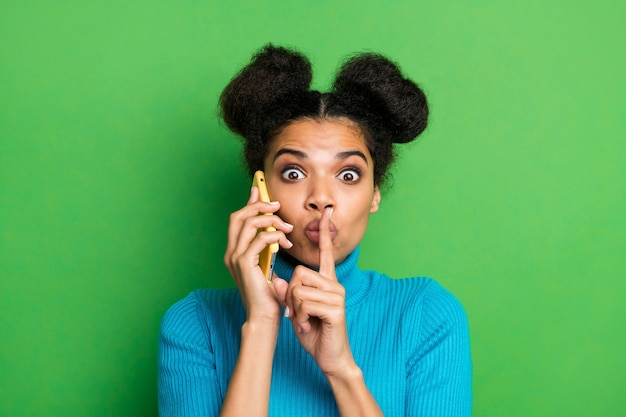 Funny lady hold telephone speaking hold finger on lips mouth