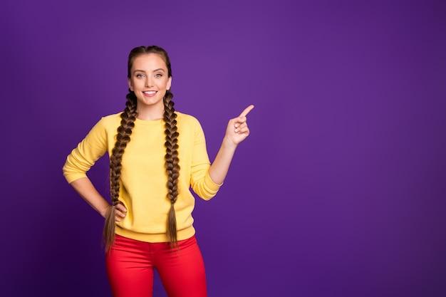 Забавная дама с длинными косами прическа, указывая пальцем на пустое пространство
