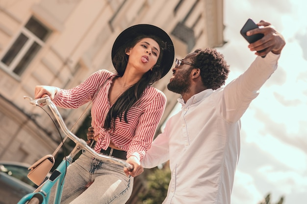 Funny lady showing tongue and smiling man taking selfie with her