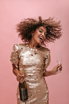 Funny lady in stylish beige dress holding bottle with champagne and glass and playing her curly fluffy hair on isolated wall..