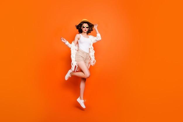 Смешная леди летнее время прыгает высоко, наслаждайтесь видами курорта, отправляя поцелуи, носите шляпу от солнца, белые кружевные пляжные шорты.