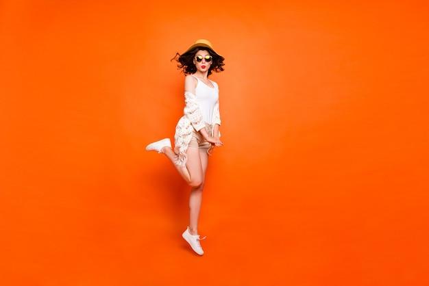 面白い女性の夏の時間は高くジャンプし、キスを送信するリゾートの景色をお楽しみください太陽の帽子白いレースのビーチスタイリッシュなケープショーツを着用してください。