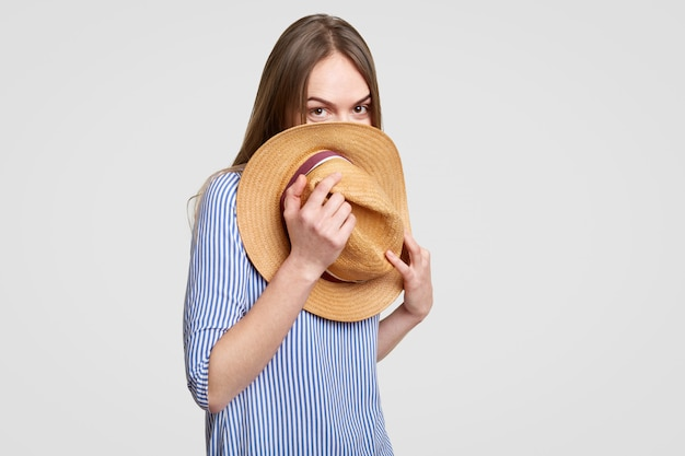 Funny lady with dark straight hair, hides behind straw hat, has fun, dressed in stylish blouse, isolated over white