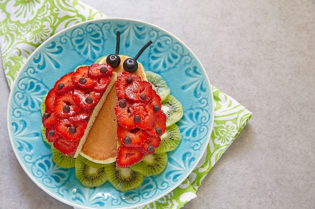 Funny ladybug pancakes with berries for kids breakfast