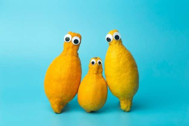 Funny lemons with eyes on a blue background.   ugly food and ugly vegetables concept, food for kids (children), food face.