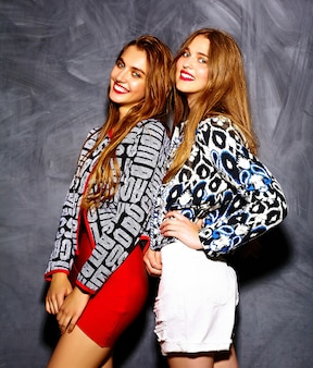 Funny lifestyle crazy glamor stylish sexy  smiling beautiful young  women models in summer bright hipster cloth  near gray wall