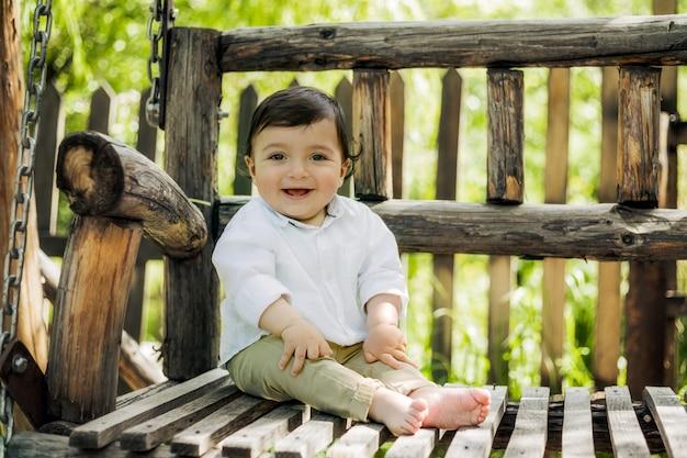 Забавный маленький мальчик сидит в саду на деревянной скамейке-качелях и смеется перед камерой