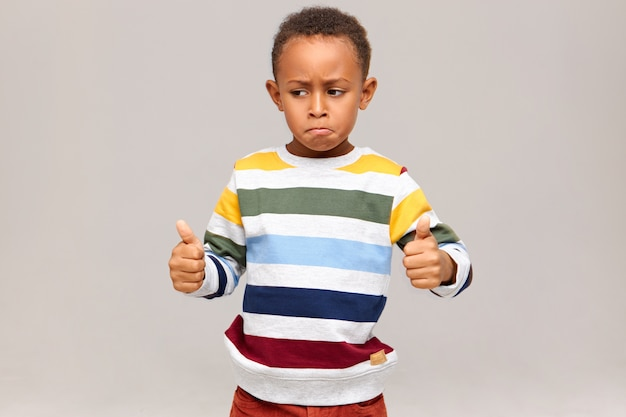 Funny little african american boy in striped pullover posing  giving thumbs up, saying well done, praising someone for good excellent job, success at study or work. black child approving