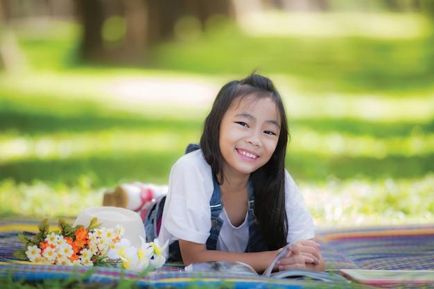 面白い小さなアジアの女の子が庭で眠る