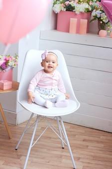 Смешная маленькая девочка в розовом ярком современном интерьере.