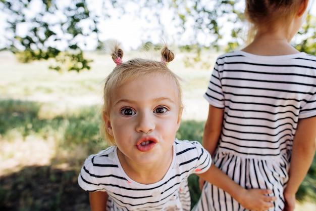 面白い小さな女の赤ちゃんがカメラに目を大きく見ます