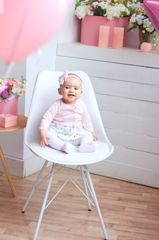 Funny little baby girl in pink bright modern interior.