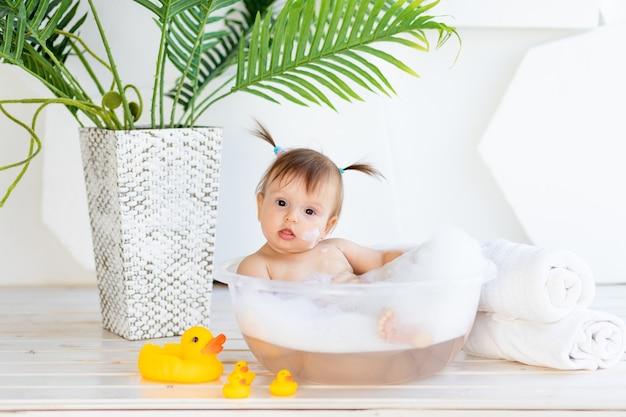 Забавная маленькая девочка моется в тазике с пеной и водой в светлой комнате дома