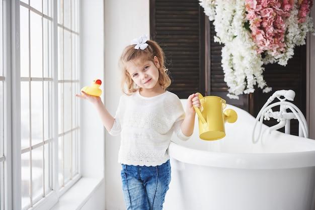 巻き毛の面白い小さな女の赤ちゃん。お風呂に入る準備をしなさい。広々とした明るいバスルーム。健康で清潔な体。子供の頃から自分の世話をする