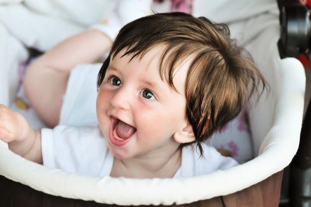 乳母車に横たわっている面白い小さな赤ちゃん