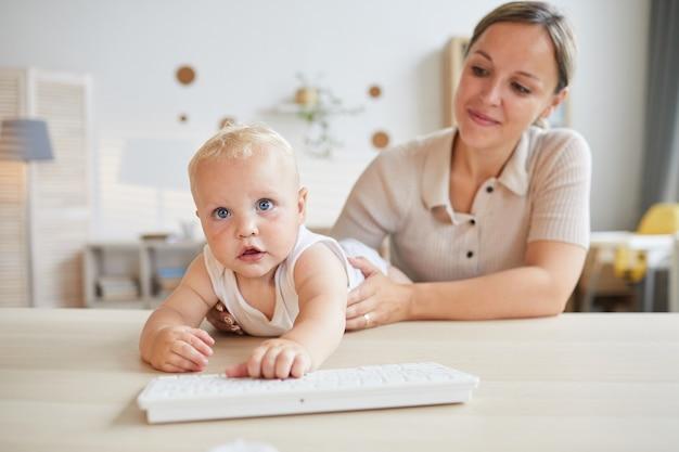 Забавный маленький ребенок пытается играть с компьютерной клавиатурой, пока мать держит его, горизонтальный снимок