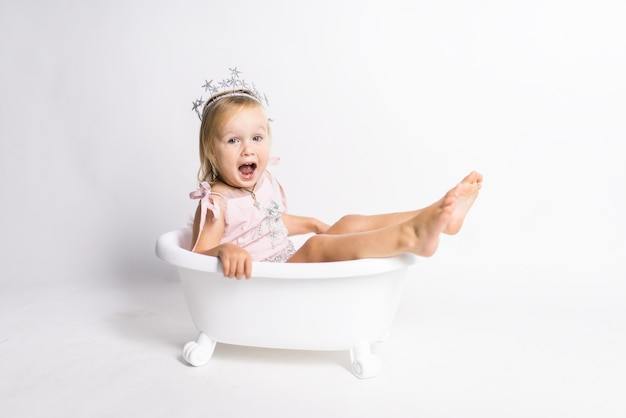 Funny little blonde girl sits in a bath in the studio