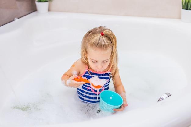 Смешная маленькая белокурая девушка принимая жемчужную ванну в красивой ванной комнате. детская гигиена. шампунь, лечение волос и мыло для детей.