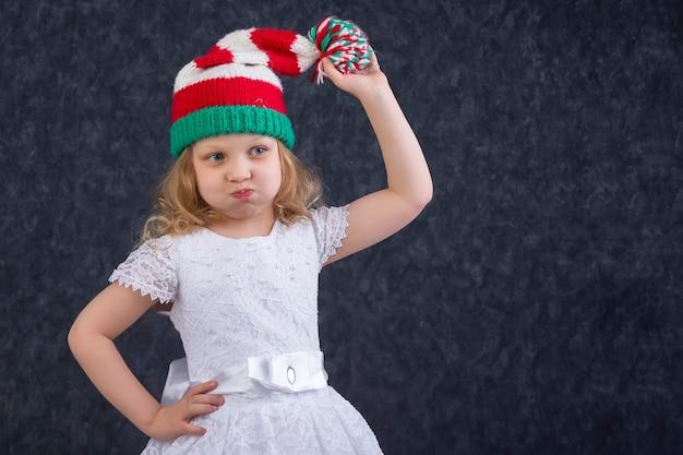 Забавная маленькая блондинка в вязаной новогодней шапке с помпоном. счастливый красивый ребенок около пяти лет.