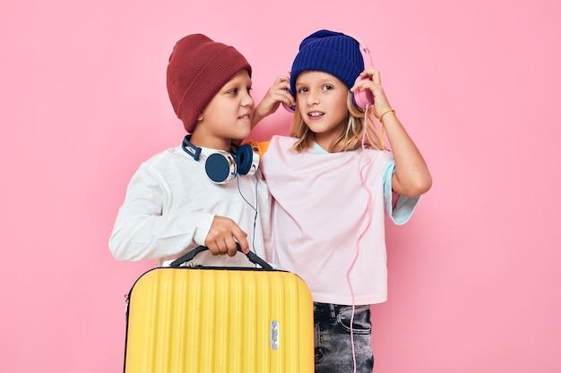 休日の準備をしている面白い小さな男の子と女の子若い旅行者は背景を分離しました