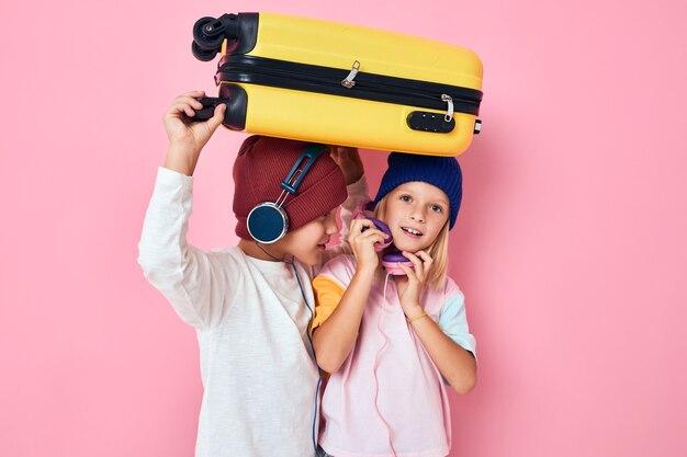 面白い小さな男の子と女の子の休日の準備若い旅行者ピンク色の背景