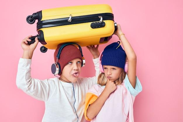 面白い小さな男の子と女の子のスタイリッシュな服スーツケースヘッドフォン分離された背景