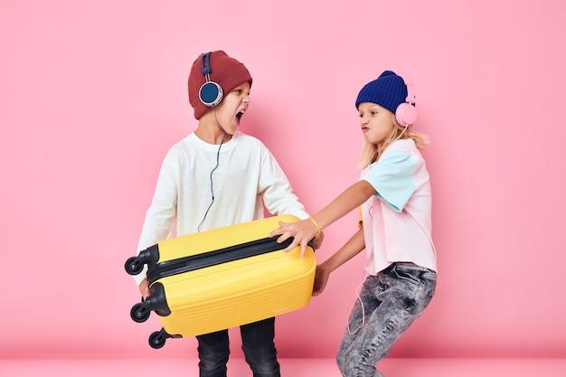 ヘッドフォン分離された背景を持つ面白い小さな男の子と女の子の黄色のスーツケース
