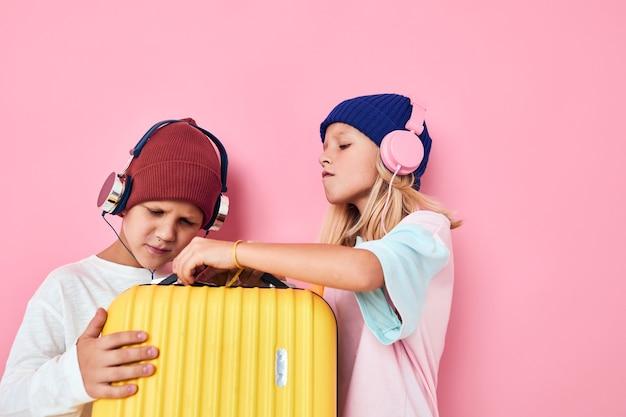 ヘッドフォンピンク色の背景を持つ面白い小さな男の子と女の子の黄色のスーツケース