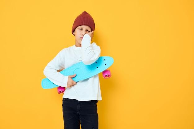 Funny little boy casual blue skateboard studio posing