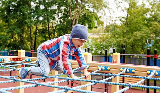 재미있는 소년 놀이터에 밧줄 웹을 올라 프리미엄 사진