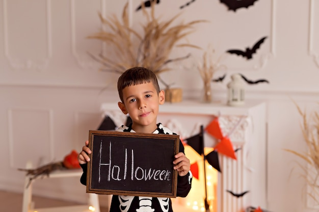 Забавный маленький мальчик девочка в костюме скелета на хэллоуин с тыквенным гнездом и метлой в помещении