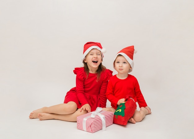 Funny little boy and girl in red caps with christmas gifts on white wall with space for
