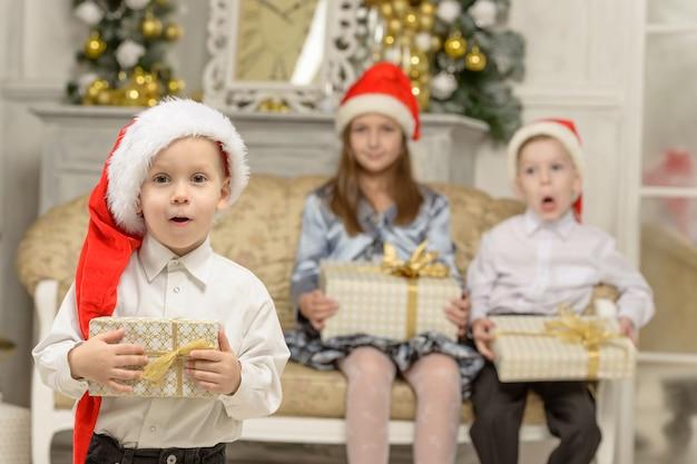 面白い男の子はクリスマスプレゼントを持っています。背景の上に幸せな子供たち