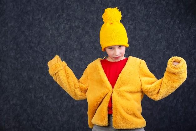 푹신한 노란색 모피 코트와 회색 배경에 니트 모자에 재미 있는 어린 소년.