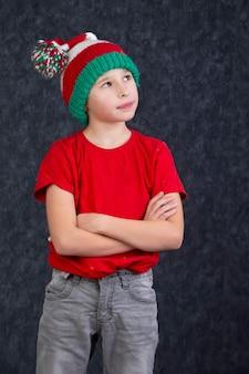 Забавный маленький мальчик в вязаной рождественской шапке на сером фоне.