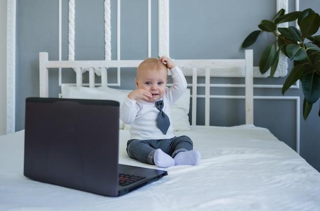 Забавный маленький мальчик в костюме сидит на кровати с ноутбуком