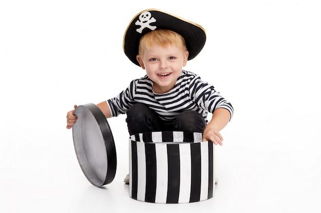 Забавный маленький мальчик в карнавальных костюмах пиратов стоит с большой тыквой на белом