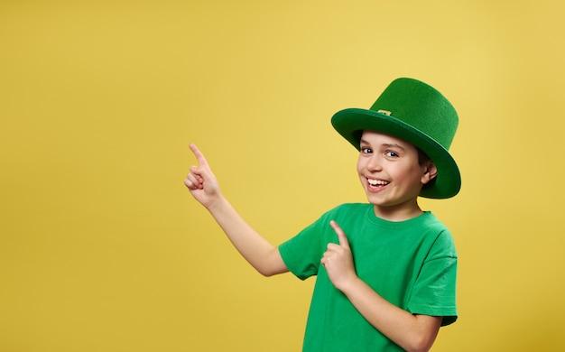 彼の指がコピースペースで黄色の表面に立っているカメラを指して見ているアイルランドのレプラコーン帽子の面白い小さな男の子