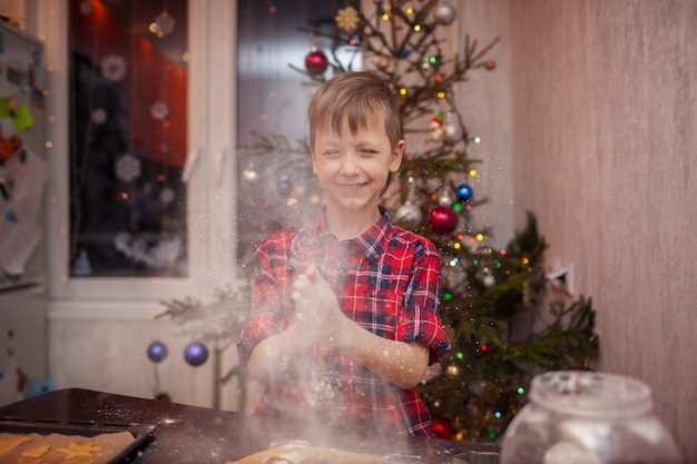 Funny little boy is preparing the biscuit, bake cookies in the christmas kitchen.