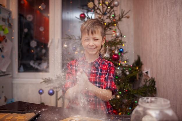 Забавный маленький мальчик готовит печенье, печет печенье на рождественской кухне.