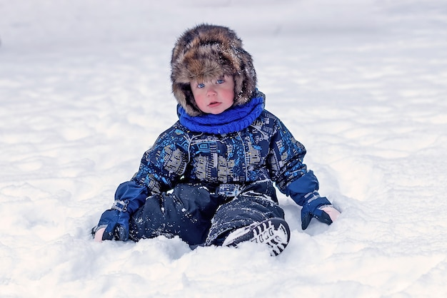Funny little boy in overalls and fur hat clothes playing outdoors during snowfall. active rest with children in winter on cold snowy days. happy child.