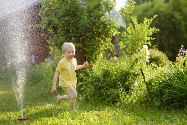 Funny little boy playing with garden sprinkler in sunny backyard
