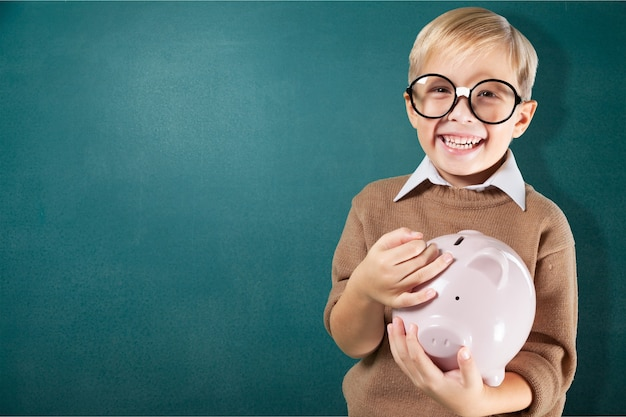 Funny little boy in round spectacles with piggy bank and green chalk board on background