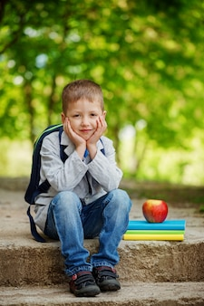 Funny  little boy sitting on stone with books, apple and backpack  on green nature background. back to school concept.